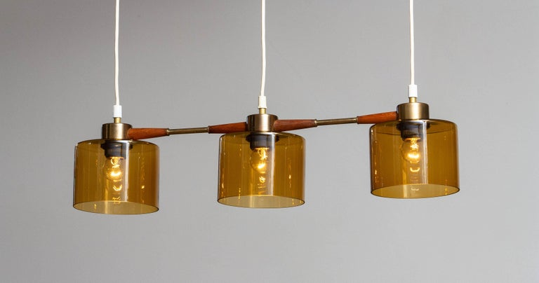 Beautiful three lights pendant with amber glas in combination with brass and teak designed by Carl Fagerlund for Orrefors Sweden. In allover good condition. Consists three screw fitting for E26 / 27 screw bulb.