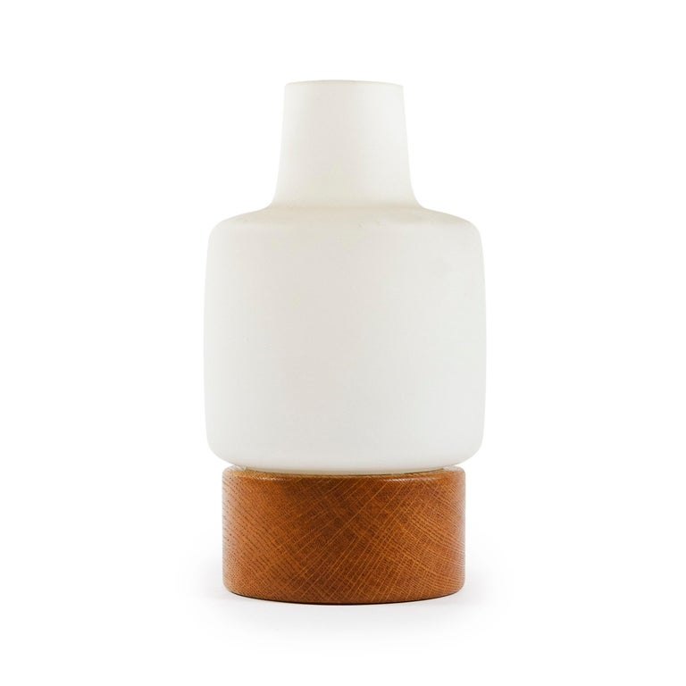 A petite table lamp with a white matte translucent glass shade resting on a rounded oak base.