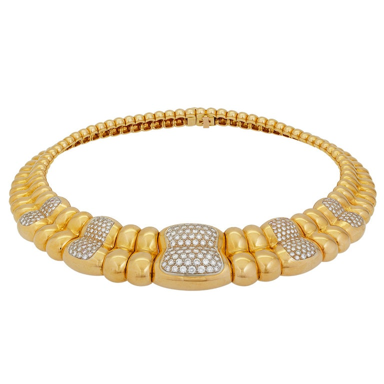 Composed of entwined three colour gold curbs, the fourth pavé-set with alternate brilliant-cut diamonds, French assay marks and concealed clasp, by Poiray Paris. Vintage.