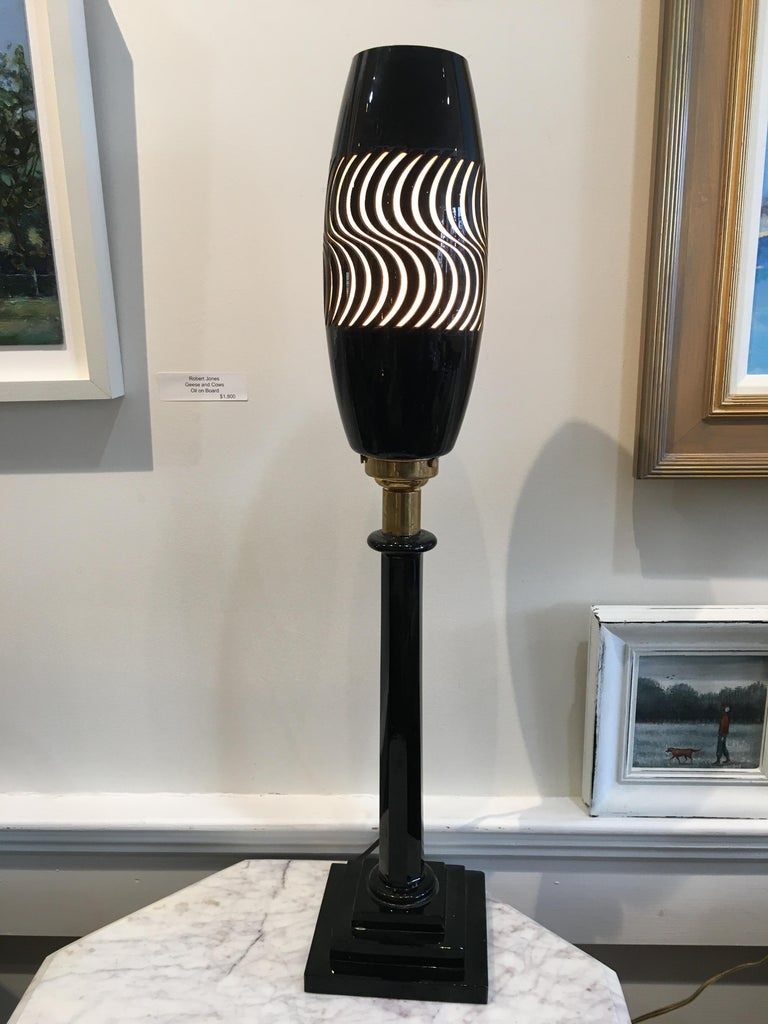 A very cool 1960s psychedelic table lamp in black glass and brass. Most of the lamp is black glass including the base, and brass where the light fixture component attached. The black glass shade has been cut away making a cool pattern that is backed