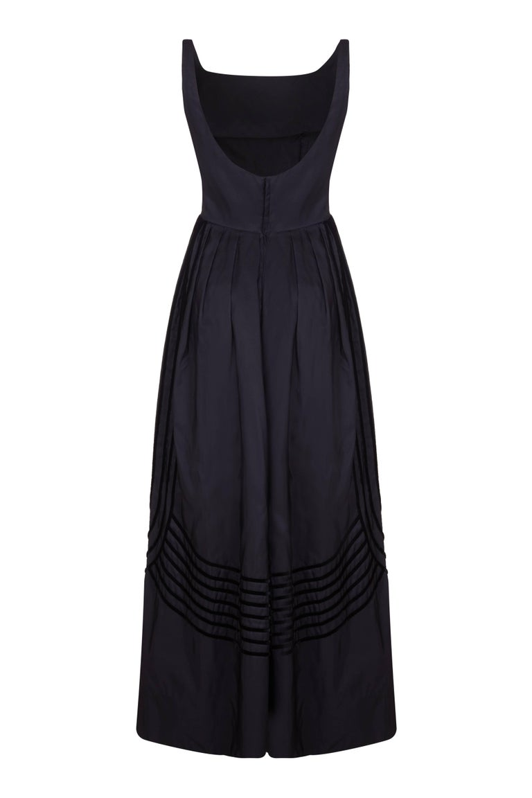 This gorgeous full length, sleeveless ball gown by Rappi in black silk taffeta was made for New York department store Lord and Taylor.  Dating from the late 50s/ early 60's this beautiful vintage piece features black velvet ribbon down the sides and