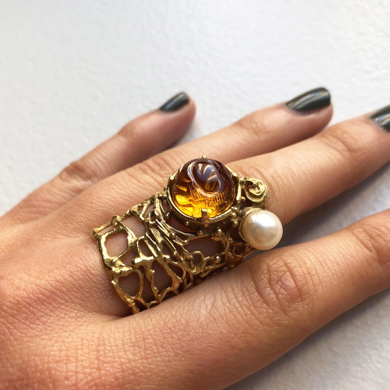 A collectible carved citrine, cultured pearl and 18 karat gold ring, by Gerda Flöckinger, c. 1965. The ring measures a size 6, and is 1.3