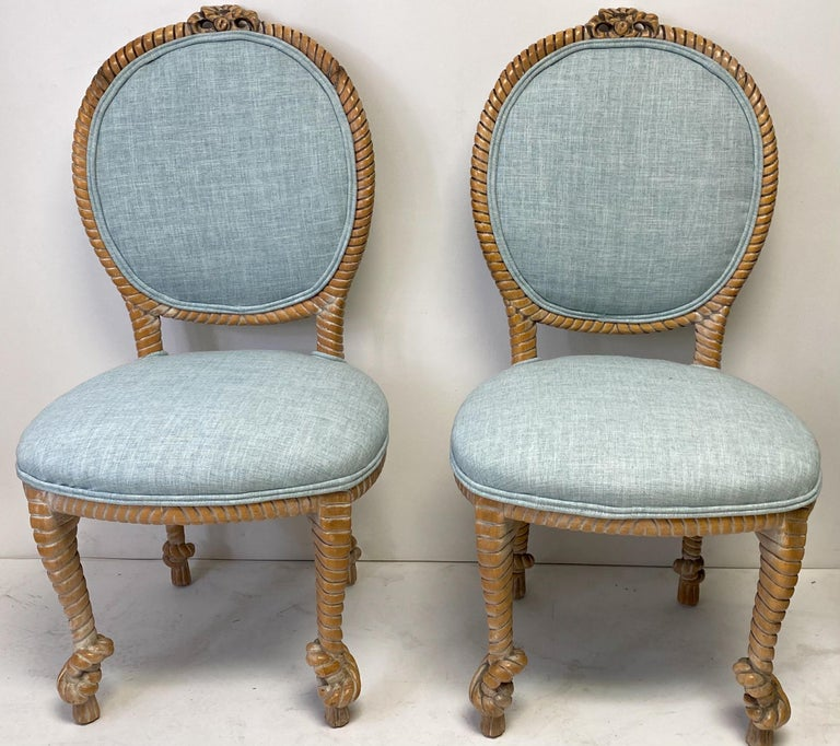 This is a pair of carved oak regency style rope side chairs by Baker Furniture Company. The turquoise linen upholstery is new. They are marked, and the frames do show some lite wear.