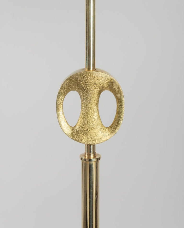 Tripod floor lamp designed by Riccardo Scarpa, presents an interesting Brutalist gilded bronze sculpture on the upper part. Cylindrical shade in off-white cotton. A lightbulb. Signature
