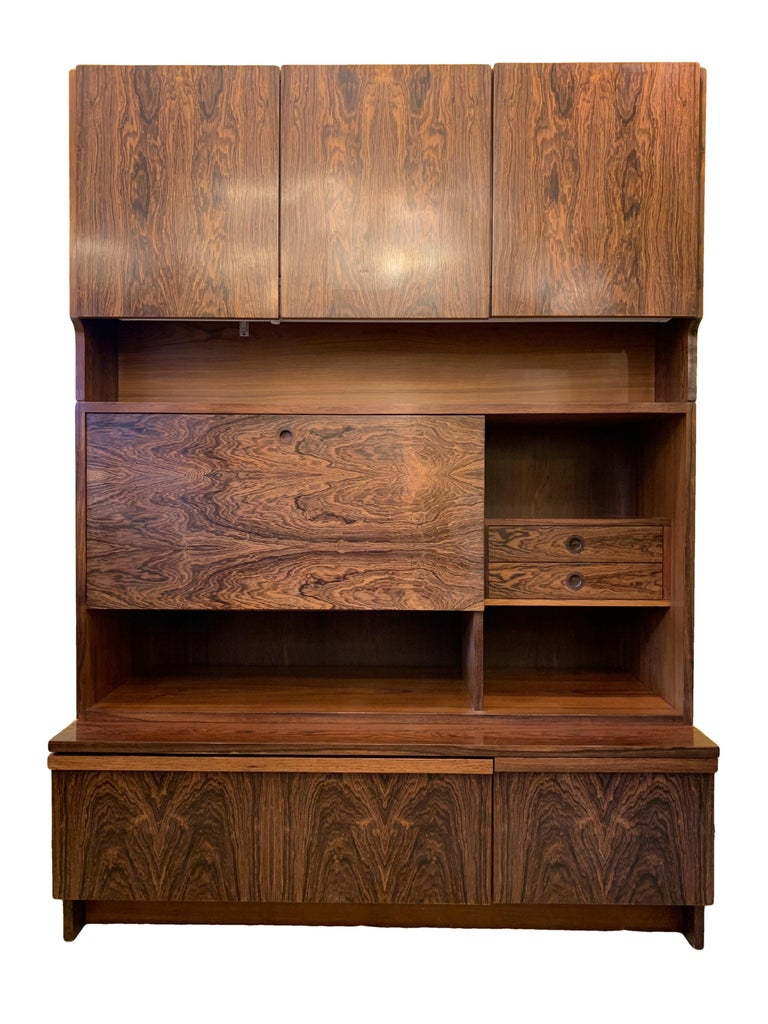 Vintage rosewood wall unit originally sold in Heals, designed by Robert Heritage in 1957 and manufactured by Archie Shine. British made. The large but compact wall unit has three doors along the top concealing a double and single cupboard. A folding