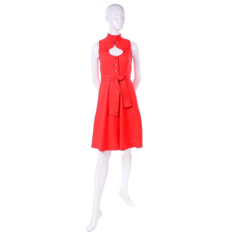This is a gorgeous dead stock vintage dress by Rodrigues from the 1960's!  This fun, sleeveless dress is in a fiery red/orange raw silk with a button closure at the neck. The dress has a keyhole cutout below the collar and two button flaps from the