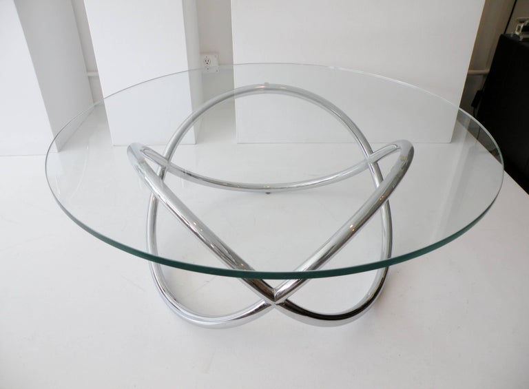 Sculptural modernist chrome and glass round coffee table. A knotted tubular pretzel twist chrome-plated base 27