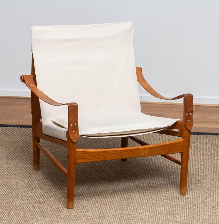 Beautiful safari chair designed by Hans Olsen for Viska Möbler in Kinna, Sweden. This chairs are made of oak with a new canvas upholstery. It is in a wonderful condition and marked. Period 1960s. Dimensions: H 81 cm, W 73 cm, D 70 cm, SH 38 cm.