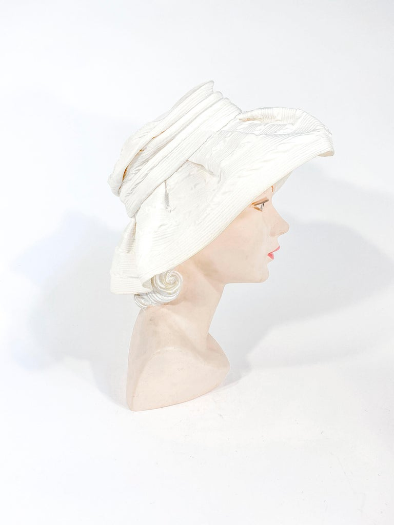 1960s off-white fashion hat with wide unstructured brim gathered on the crown. The till textile has a fine circular topstitching that wraps around the hat.