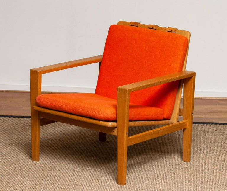 Comfortable Scandinavian lounge chair designed by Erik Merthen for Ire Skillingaryd, Sweden, 1960s. The oak frame is in perfect condition as well as the leather belts who supports the backrest. The cushions have been newly filled. The overall