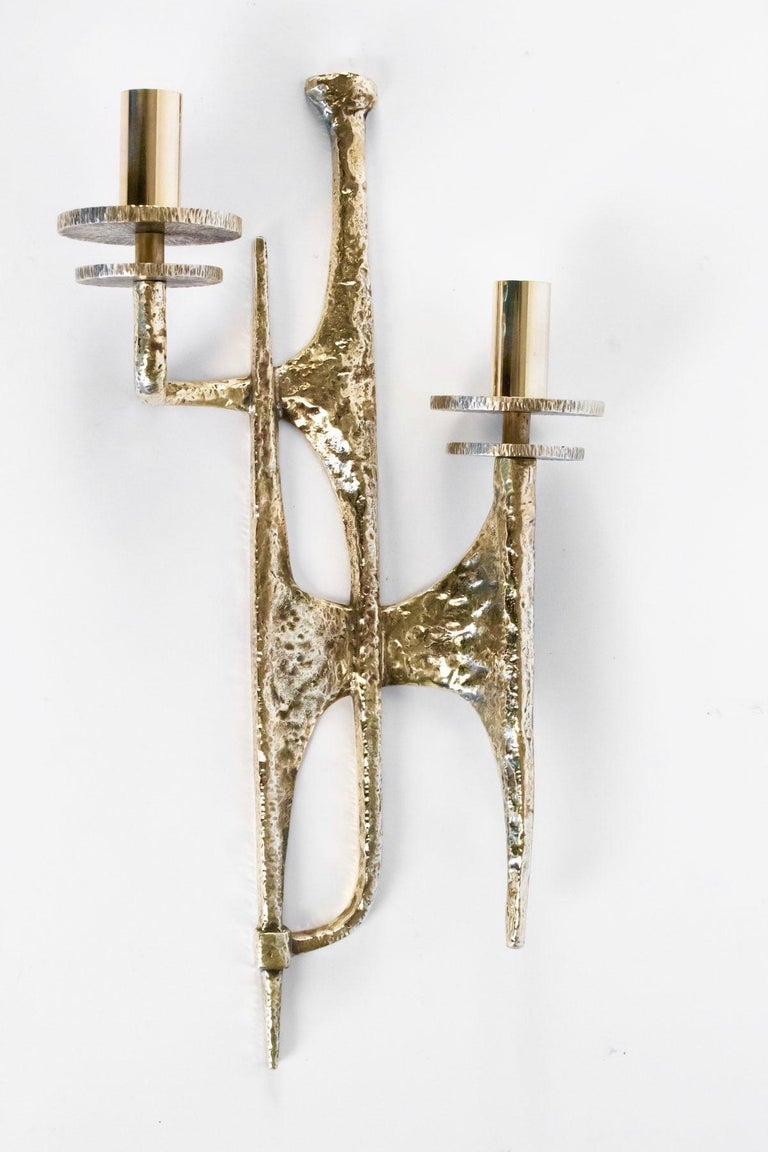 Each sconces features two lighted arms which form an asymmetrical pattern. 