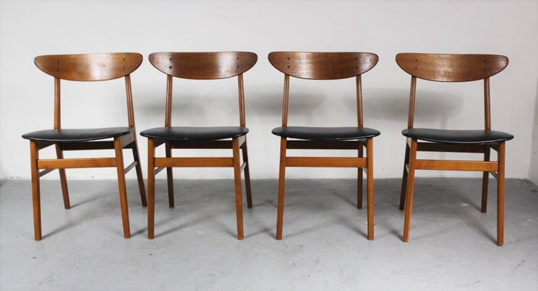 Set of four dining chairs from the 1960s from Denmark. Material is teak and beech, upholstered with faux leather. Chairs are in very good condition.