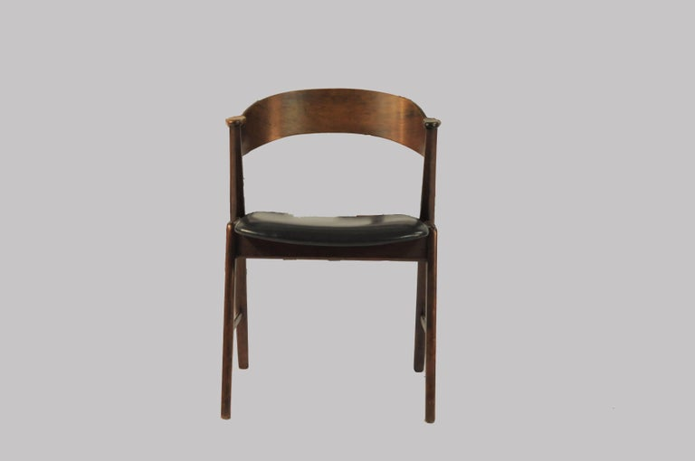 Set of six dining chairs with curved rosewood backrests sliding into rosewood armrests and elegant frames in teak.   The elegant comfortable and well crafted chairs have been checked, restored if needed and refinished by our experienced cabinetmaker