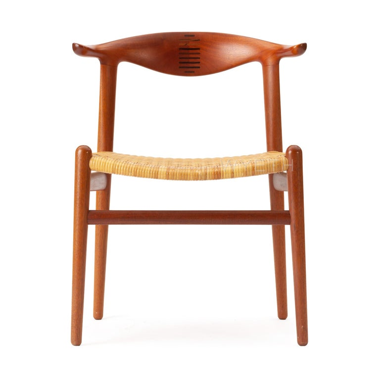 A set of (10) rare teak 'cow Horn' dining chairs with splined backrests and caned seats. Model JH-505.