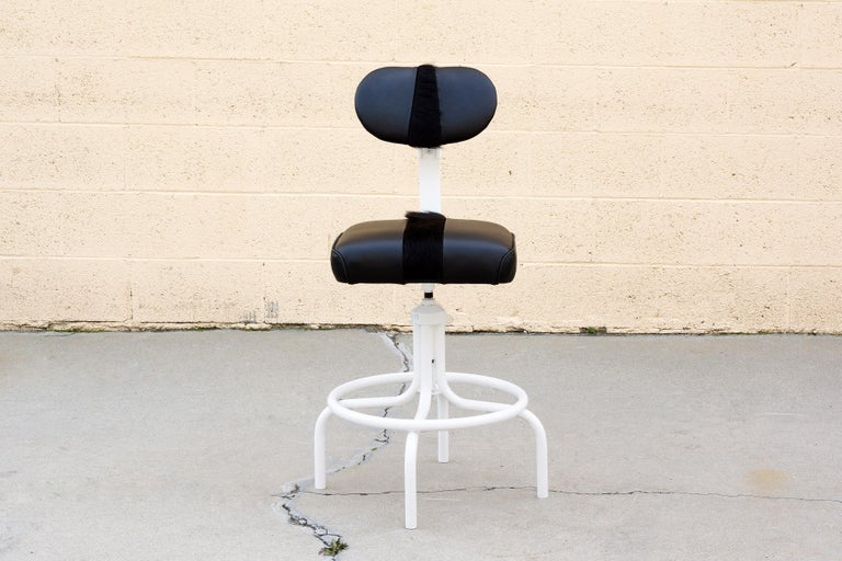 1960s Industrial style drafting stool in two-tone black on white. Frame refinished in gloss white powder coat and seat upholstered in a combination of leather with cowhide detail. Most unique!  Dimensions: 16