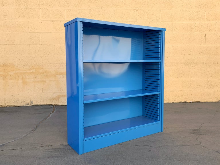 Neat 1960s tanker style steel bookcase freshly powder coated in high gloss blue (BL05). This adjustable 3-shelf unit is an excellent storage option– its sleek and compact, yet holds many books. It's perfect for storage and display. Please not this