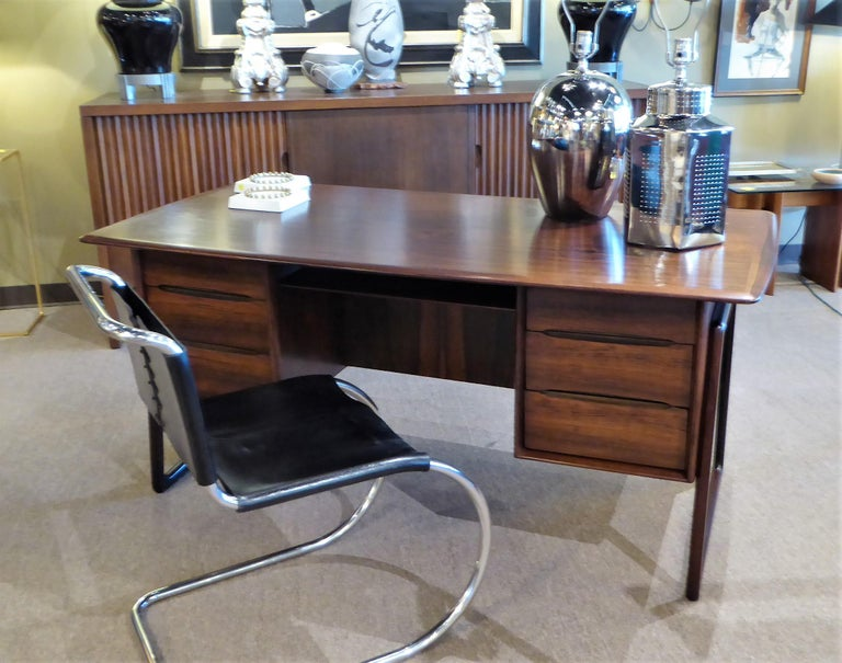 Fine and beautifulrosewood desk designed by Svend Aage Madsen in Denmark. With a floating style top over three drawers left and right and a pass through shelf, front to back. The back side with a deep shelf for books or whatnot. Supported on