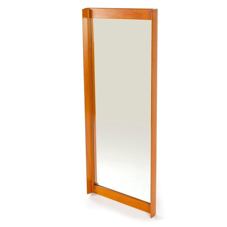 An elegant wall mirror manufactured in Sweden with a handcrafted teak-frame with bowed sides and original glass.
