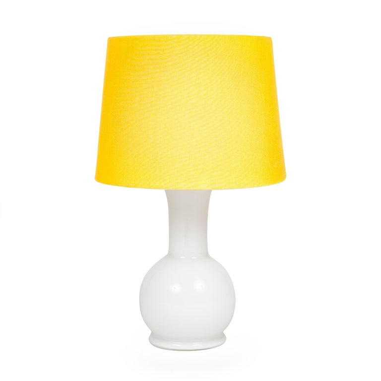 Bulbous glass table lamp of diminutive stature of opaque white glass beneath a white acrylic upper section which acts as both a diffuser for the light source as well as a holder for the shade which conceals it.