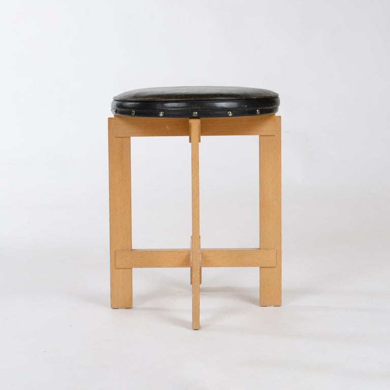A four-legged solid oak stool with X-shaped, lap-joined stretchers highlighted by their tongue and groove joinery to the legs, having a simple original leather-upholstered circular seat. Marked with original LUXUS sticker.
