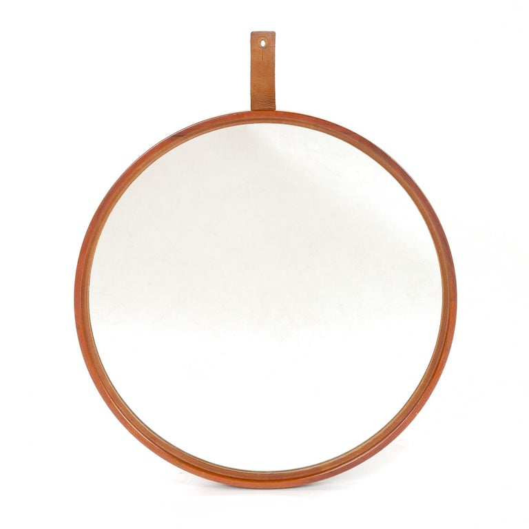 Finely crafted circular mirror set in a narrow teak frame with leather hanging strap.