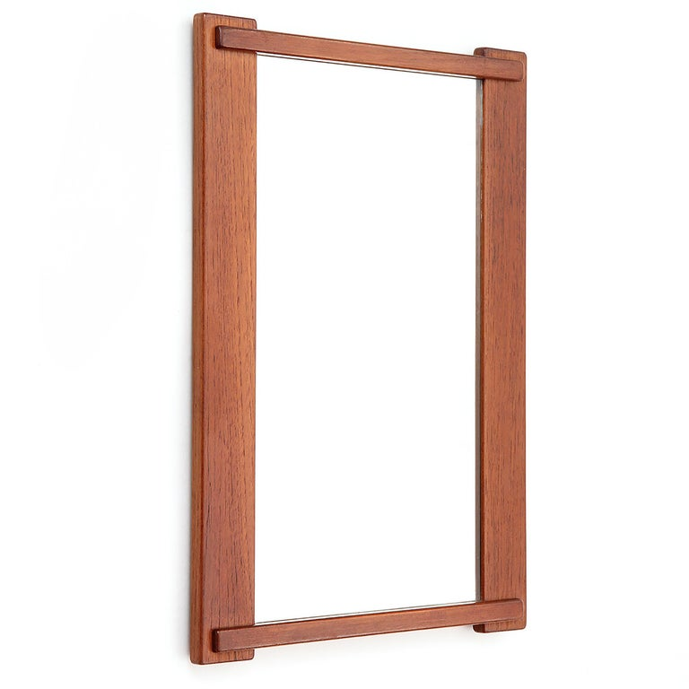 A strikingly unique mirror with overlapping top and bottom rails executed in teak.
