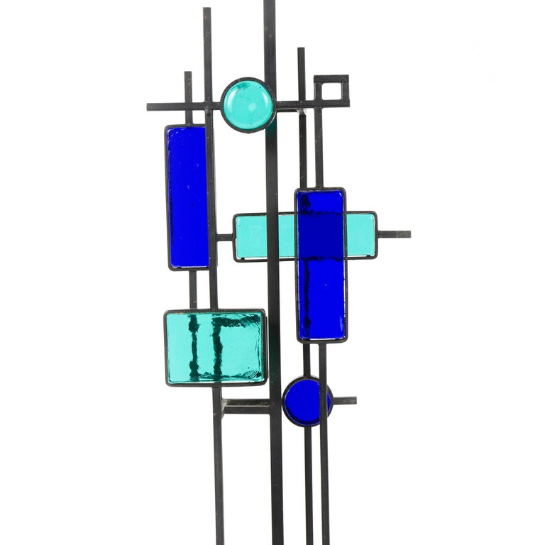 A pair of tall black wrought iron and glass floor or table lamps. Various pieces of thick green and blue glass in geometric shapes framed in black wrought iron and suspended on square thin metal rods above a square wooden base colored black.