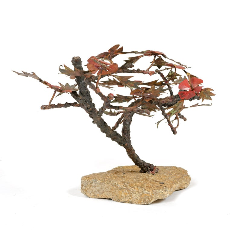 From Steck's 'Windswept' series, this table top sculpture exhibits thick, textured limbs with thinner branches displaying patinated leaves and numerous four petal flowers of an oxidized, cardinal red hue the whole set on a rugged, light color