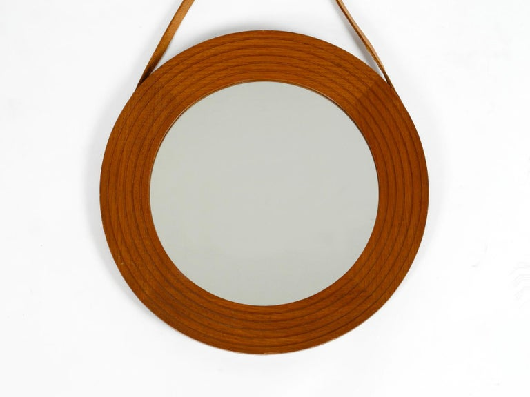 Original 1960s beautiful wall mirror with wide teak frame. The original leather strap for hanging is completely stretched around the mirror. Very high-quality workmanship in a Minimalist Danish design. 100% original condition and in very good