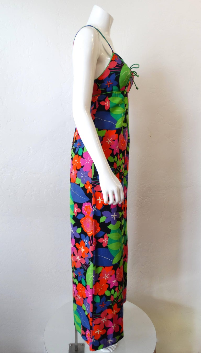 We love a good jumpsuit- and you will too with our amazing 1960s technicolor floral jumpsuit! Sleeveless, spaghetti strap fit with wide flare legs. Covered in an amazing neon leafy floral print on a black solid background. Trimmed with bright green