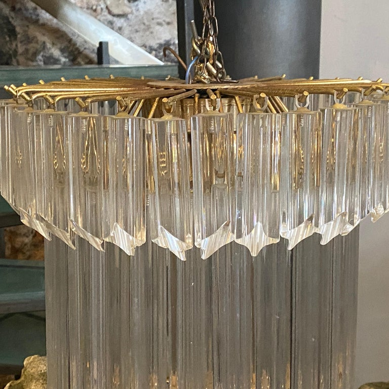 This chandelier is made up of elegant solid glass prisms mounted on a brass base. Each murano glass, giving you a soft warm light. We should note that any amount of chain can be added to customize the length of the chandelier. It's made by Venini in