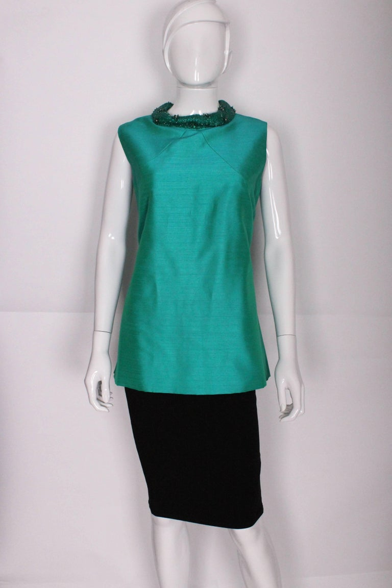 A great 1960's, long shift style top by Peter Barron. Made in a stunning rich turquoise slub silk this top is a perfect jewel toned piece. It has a stand up collar that is heavily embellished the whole way around in small glass beadwork. There are