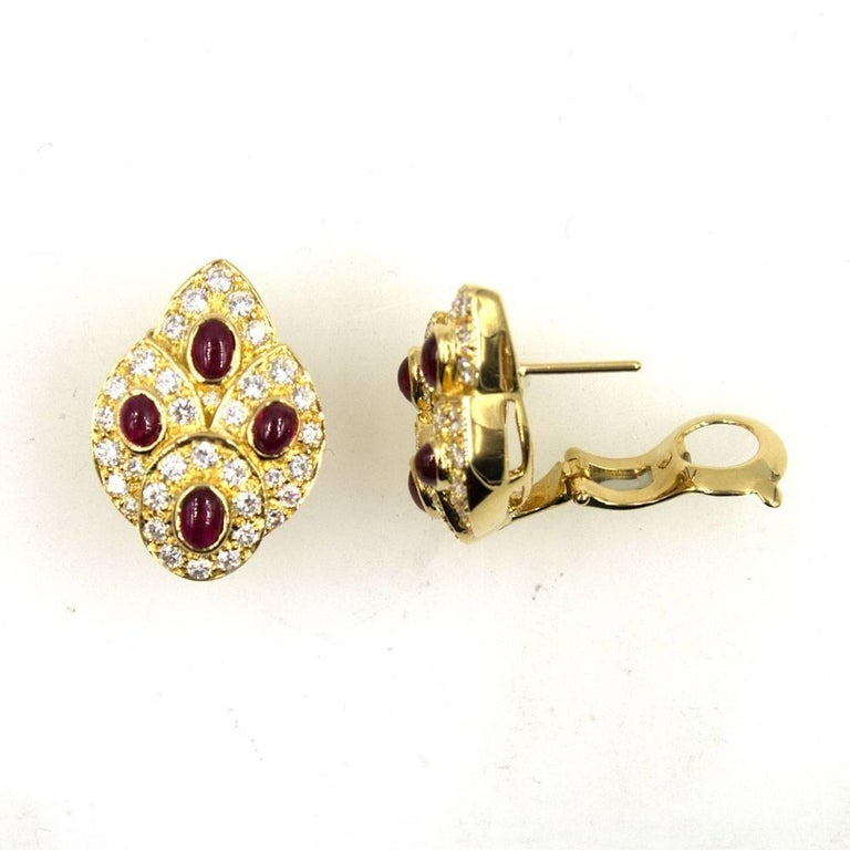 Fabulous and elegant diamond and ruby earrings by Van Cleef & Arpels. The earrings can be worn as clips or with posts (retractable posts). Two carats of sparkling round brilliant cut diamonds surround 8 cabochon bright red rubies. Fashioned in 18