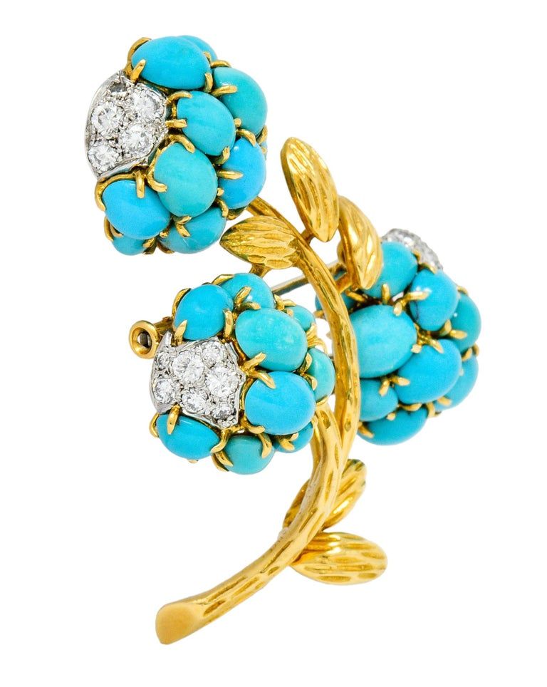 Brooch is designed as three clustered flowers blooming from a very textured gold stem  Each flower is comprised of claw set round and oval turquoise cabochon, opaque, and greenish-blue to robin's egg blue in color  Accented by platinum pavè fields