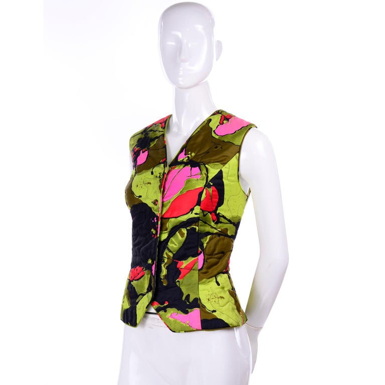 This is fun and colorful late 1960's vest from Dynasty. Wear it as a vest or as a sleeveless top, either way, it is a great piece to add to your closet! The print is an abstract floral, with splatters of army and lime green, hot pink, and red. The