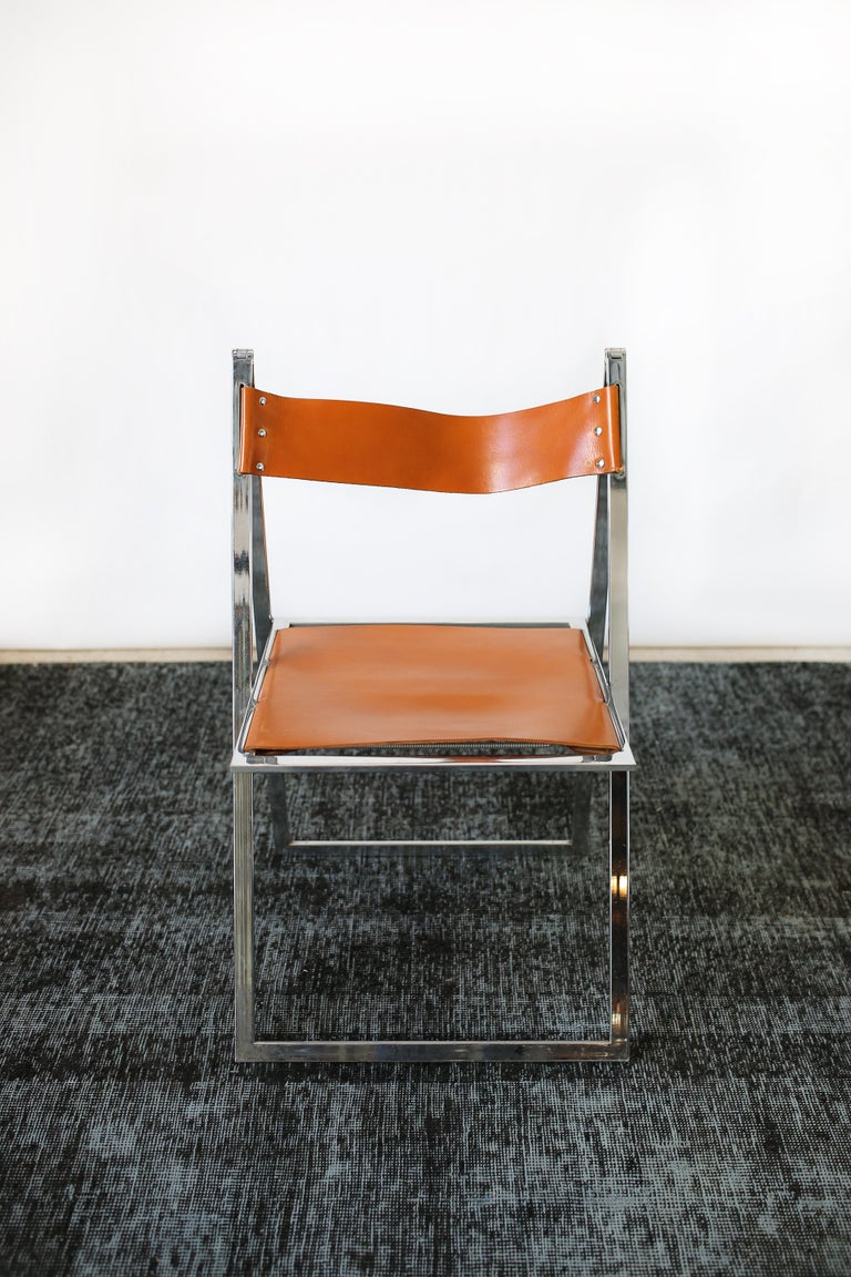 This set of ten 1960s vintage Italian chrome and leather folding chairs by Elios are in overall good condition and wear consistent with age and use.  Brilliant chrome frame.  Aged natural leather.  Vintage modern design. Original label.  Dimensions: