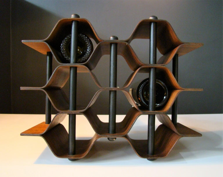 Vintage rosewood bottle holder designed by Swedish sculpture Torsten Johansson c. 1960, this 8-bottle wine rack is constructed of pressure formed, nicely figured rosewood and blackened steel supports. Beautiful and functional. A perfect addition to
