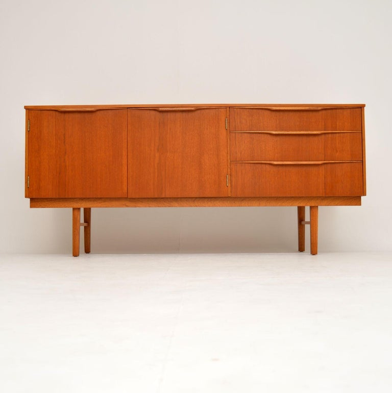 A smart, stylish and very well made vintage teak sideboard. This dates from the 1960s, and it's in superb condition throughout. We have had it stripped and re-polished to a very high standard, it has a gorgeous color and lovely grain