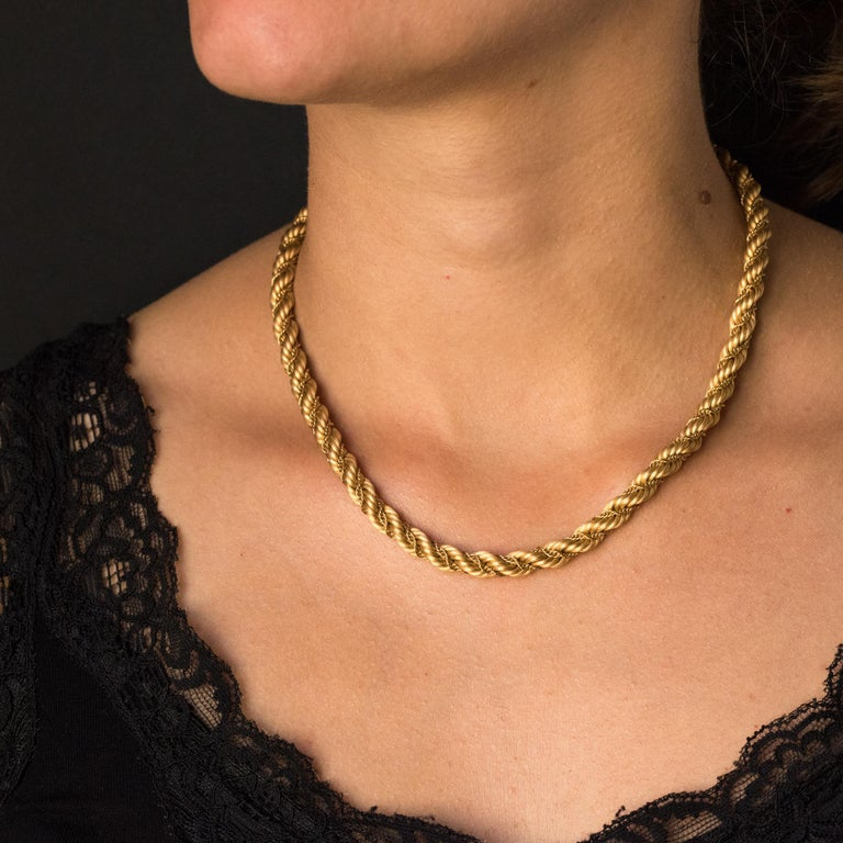 Necklace in 18 karats yellow gold, eagle's head hallmark. This vintage necklace is made of gold thread braided rope in which is wrapped a gold chain. The clasp is ratchet with 8 security. Length: 42.5 cm, diameter: 6.3 mm. Total weight of the jewel: