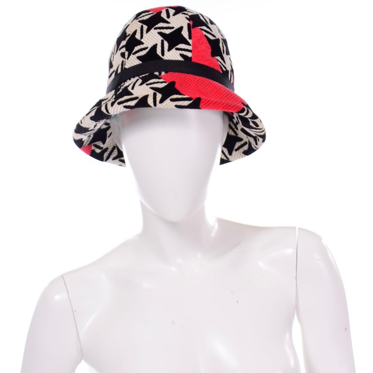 This is a rare vintage 1960's Yves Saint Laurent bucket hat in a bold, graphic print. The hat is made of velvet in a black and white modified houndstooth or pinwheel pattern print with red geometric abstract shapes and black top stitching. There is