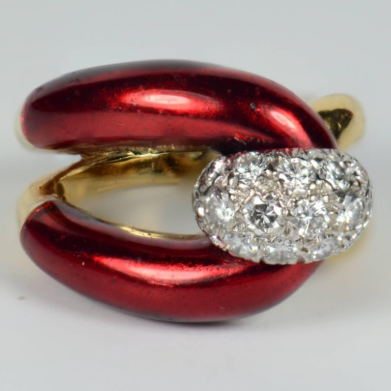 A very chic ring in 18 carat gold designed as a buckle, the uppermost part enamelled to a to a rich crimson. The bar of the buckle is represented by a diamond bombe finial in white gold pave-set with 16 round brilliant diamonds with a total