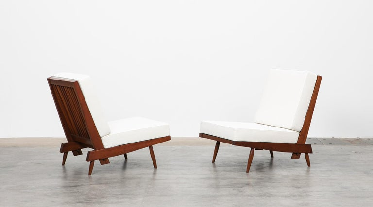 Lounge chairs, walnut, by George Nakashima  Staggering set of lounge chairs constructed with American walnut through handwork by George Nakashima himself. The light feet and frame combined with the generous seating cushions provide style and