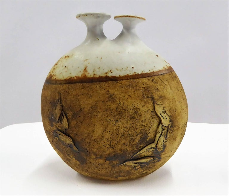 1960s art pottery vessel by Warren Hullow of Hickory Grove Studios. Fairly rare, it is a wide stoneware weed pot or twig vase with unglazed lower half and the upper glazed with a pair of spouts. Well known, he collaborated with Isabel Parks, this is