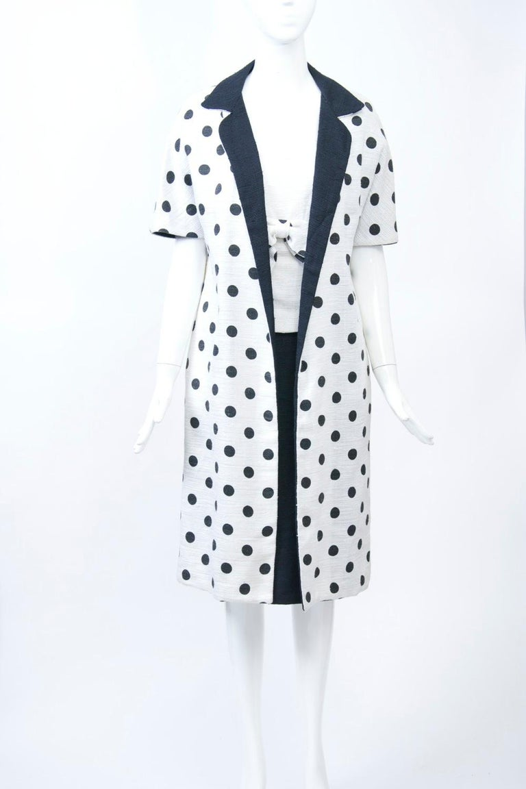 1960s summer weight dress and coat ensemble in linen-blend fabric, the short-sleeve, open coat in white with black polka dots throughout; its black lining provides the collar and facing. Underneath is a one-piece sleeveless dress that's styled as a