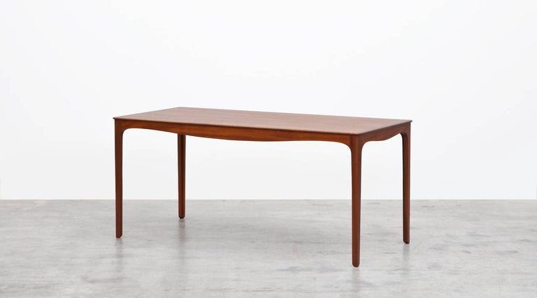 Beautifully designed side table by Ole Wanscher in teak. An elongated top with a softly curved apron above four chamfered legs. Manufactured by A.J. Iversen.  Wanschers designs aspired to preserve influences from e.g. English and Oriental