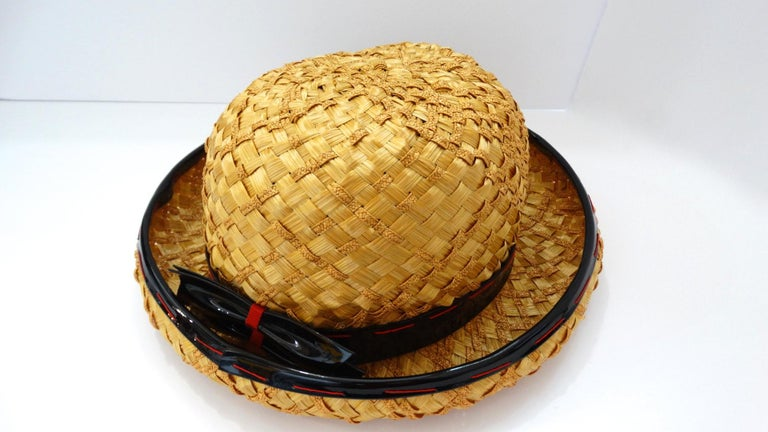 Very early 1960s Yves Saint Laurent bowler hat! Gold yellow straw, intricately lattice woven and trimmed with black patent piping. Piping sewn overtop with contrasting red thread in long, oversized stitches. Features a matching black patent bow on