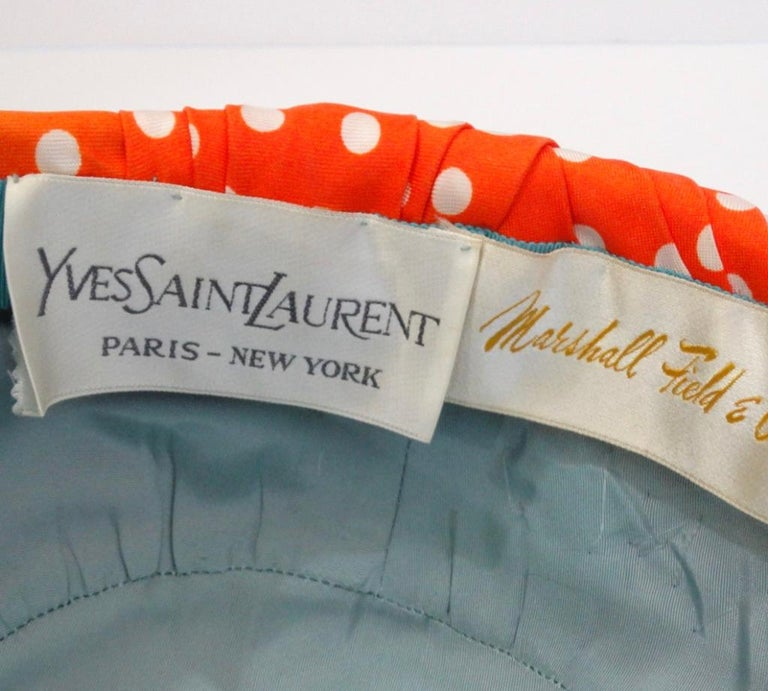 You can't say no to a good turban-especially when it's 1960's YSL! Classic turban construction made of red silk fabric complemented by white polka dots and features gathered three dimensional rose affect at the front. Sits on the head effortlessly