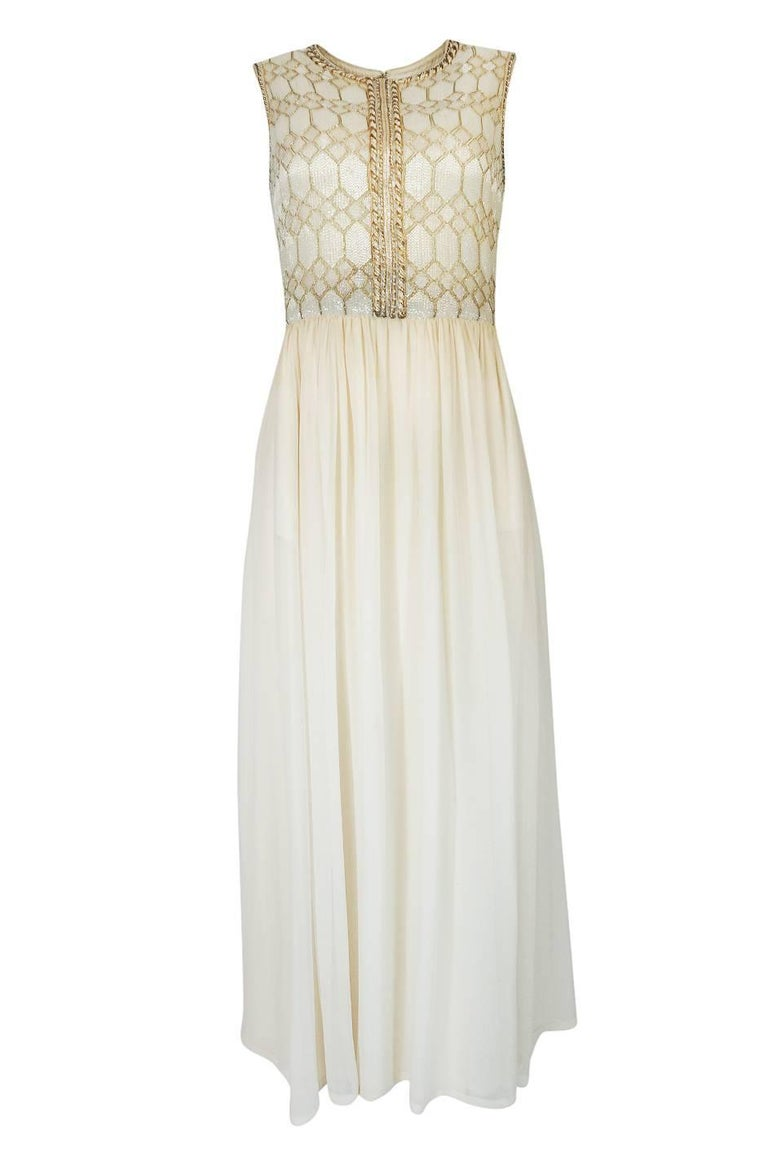 This wonderful gown with its exquisitely beaded bodice and attached cape is a numbered Haute Couture pieces designed by Pierre Balmain. It would have been  made entirely by hand at the Paris atelier. The cut of the piece is stunning in its