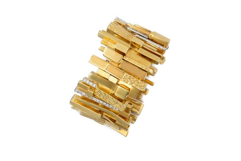 A rare mid century diamond, textured and polished 18 karat yellow gold, and platinum wide bracelet, by David Morris, 1965. The brutalist design is set with approx. 2.50 carats of round brilliant cut diamonds.  Signed David Morris.  Accompanied by