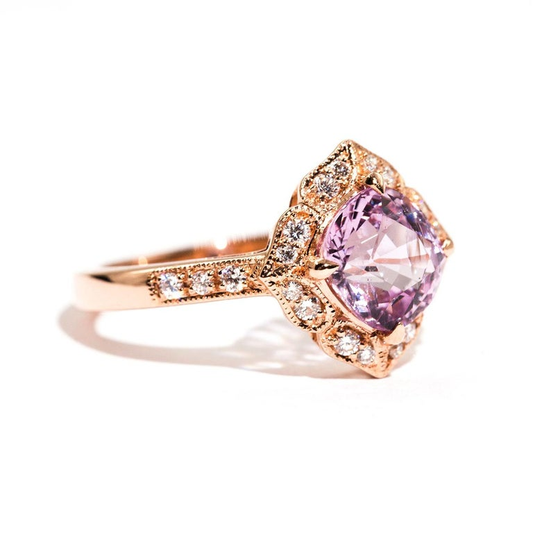 Forged in 18 carat rose gold is this vintage inspired halo ring that features an alluring 1.97 carat bright purplish pink cushion cut natural spinel complimented by a total of 0.19 carats of sparkling round brilliant cut diamonds. We have named this